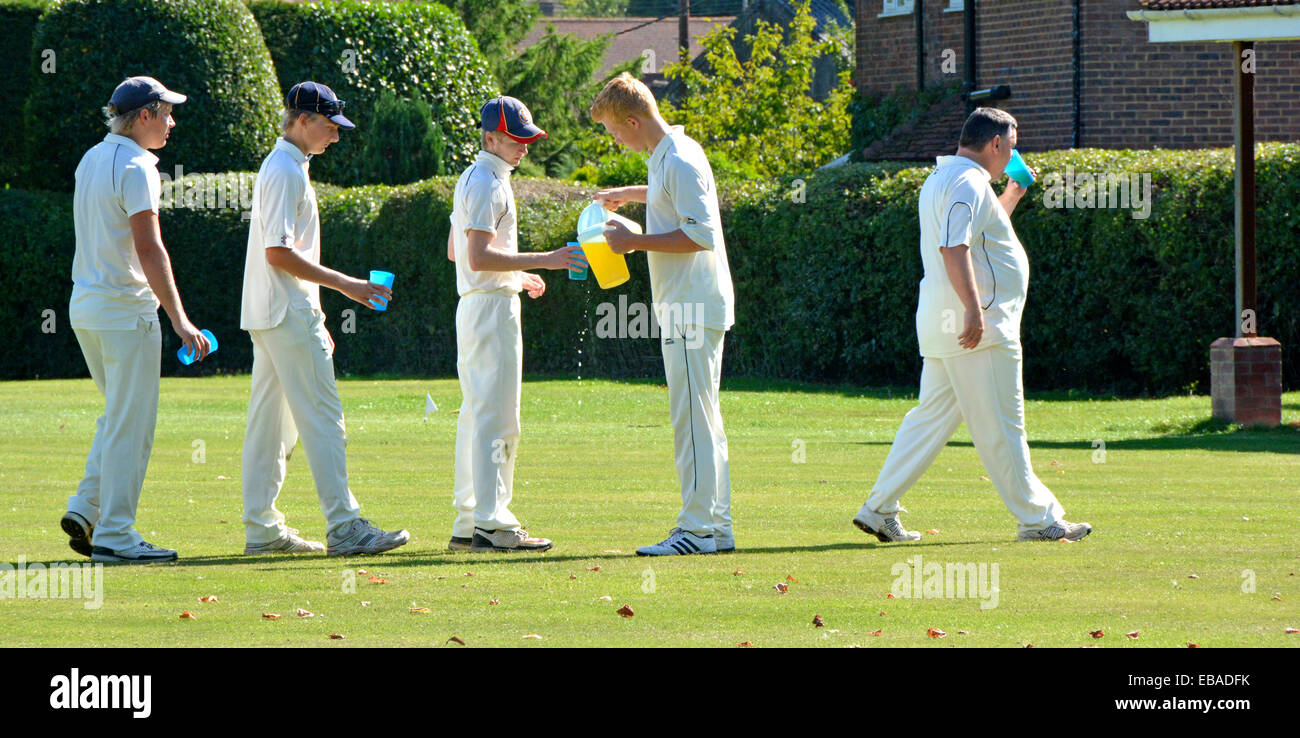 Quintessential English queue scene cricket players waiting in line taking refreshments village green match break - Stock Image