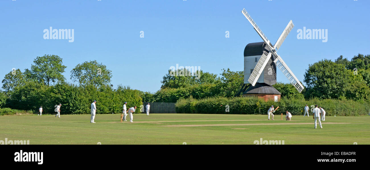 Iconic quintessential England idyllic village green cricket match bowler batsman & fielders Mountnessing Post - Stock Image