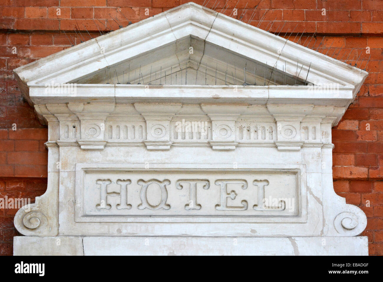 The word Hotel carved into an old stone sign mounted on a brick wall with bird scaring devices London England UK - Stock Image