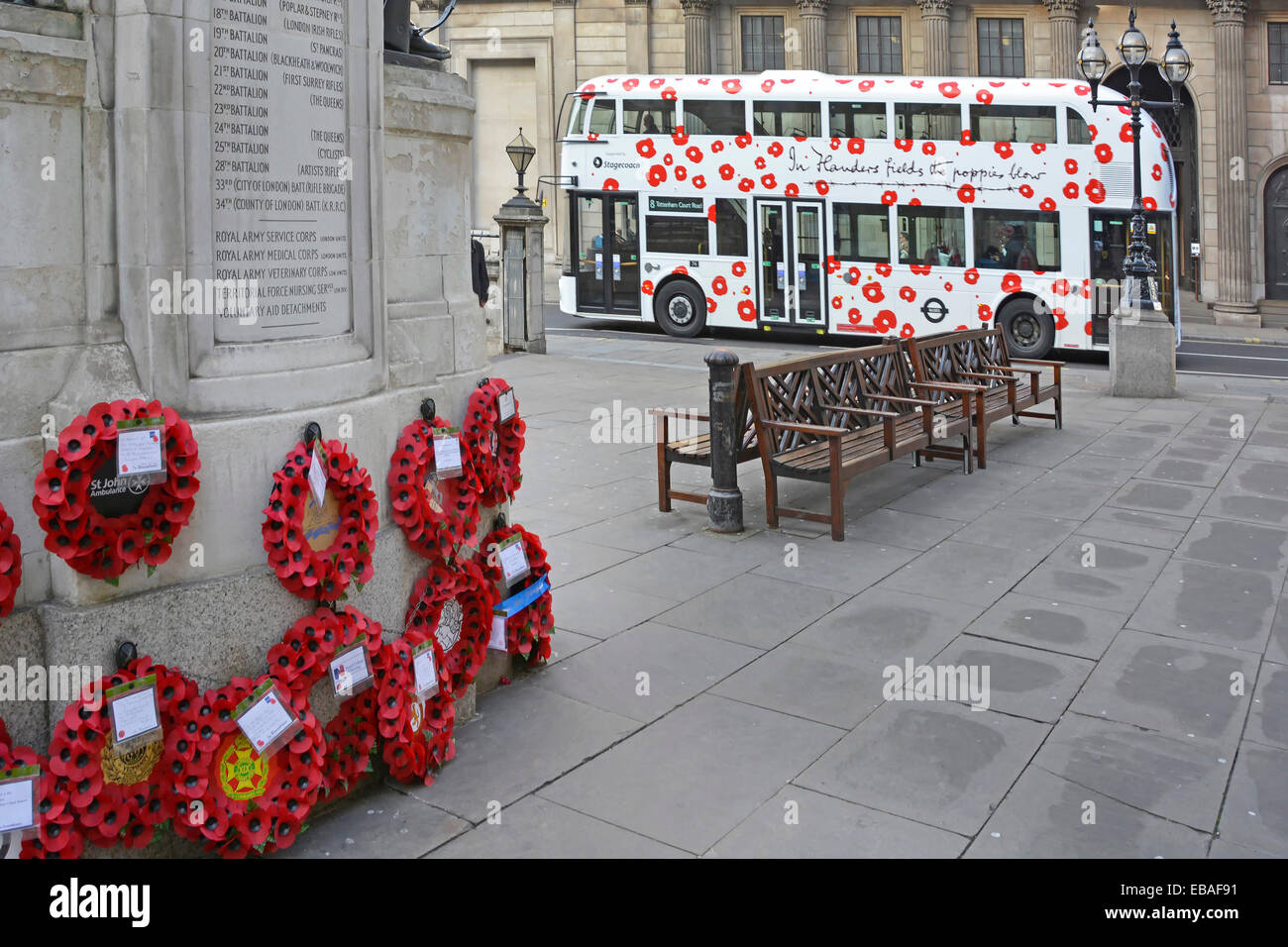New London Routemaster bus with 'Flanders Fields' poppy graphics passing the wreaths placed at the London - Stock Image