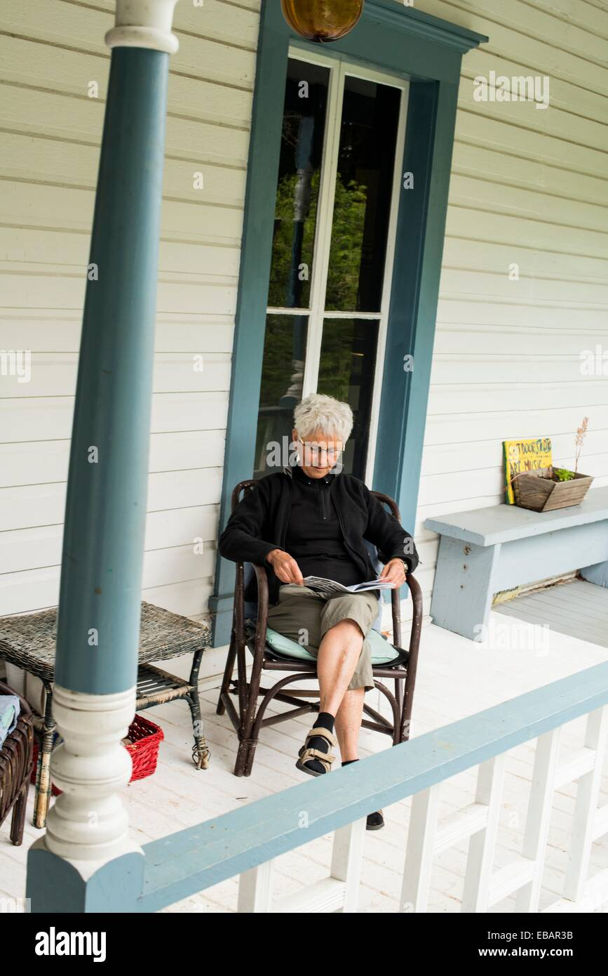 A woman 66 relaxing on the porch of the Breezy Bay Bed and Breakfast on Saturna Island Gulf Islands BC Canada. - Stock Image