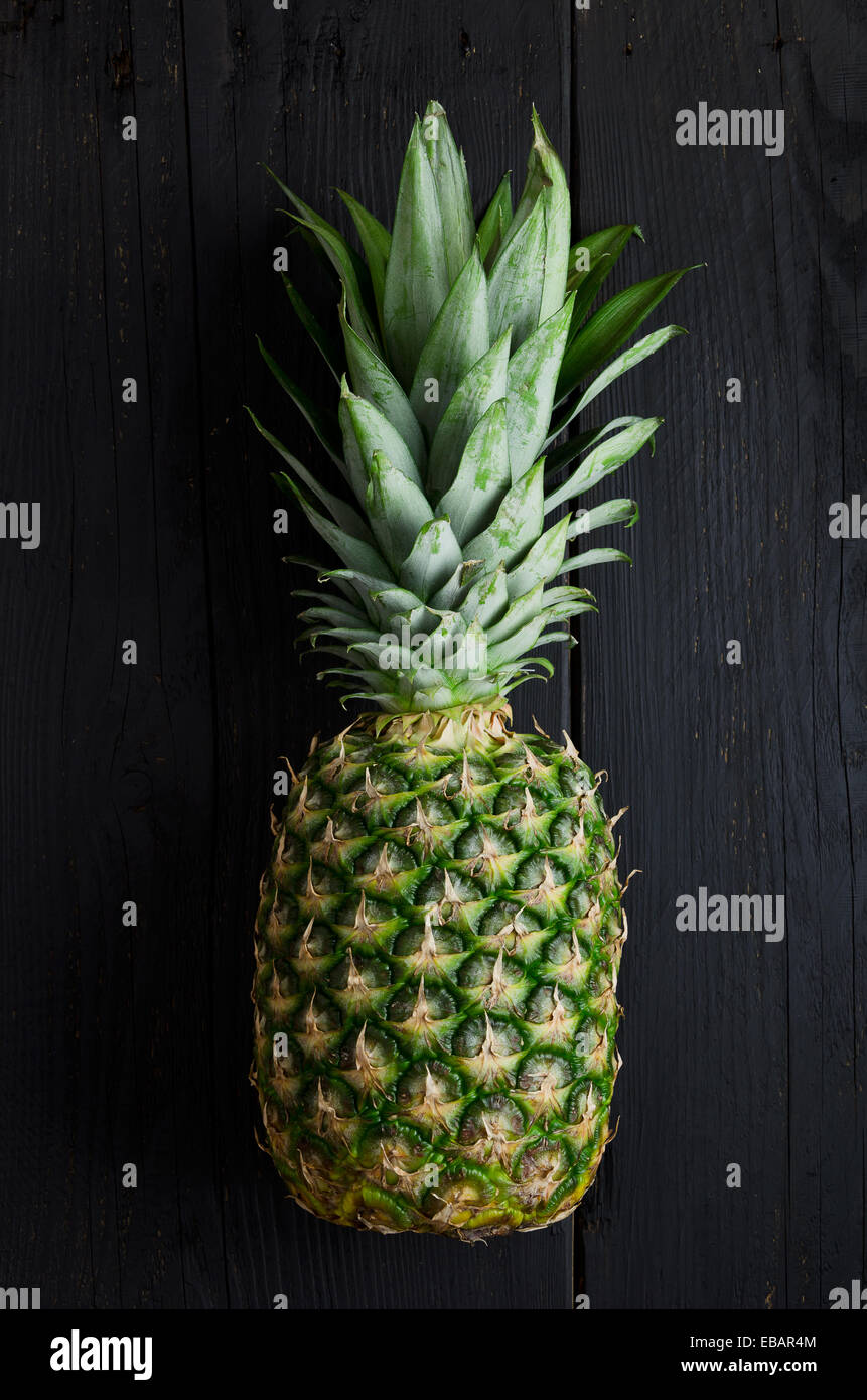 Single pineapple over black wooden table - Stock Image