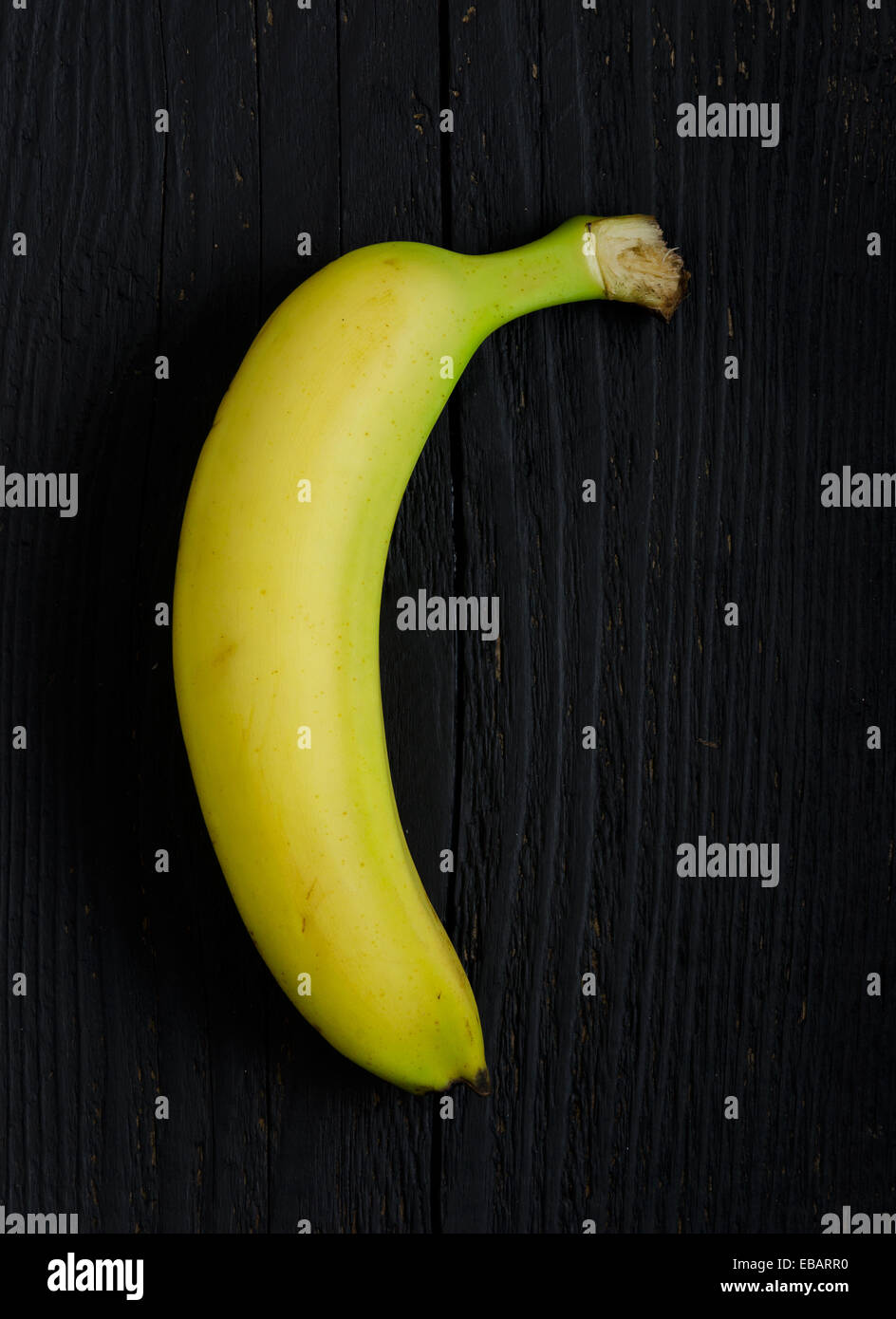 Single bananas over black wooden table, above view - Stock Image