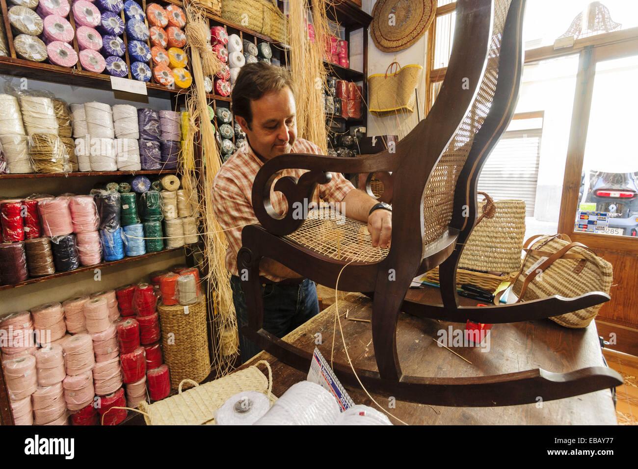craftsman weaving a wicker rocker, Mimbreria Vidal, Palma, Mallorca, Balearic Islands, spain, europe - Stock Image