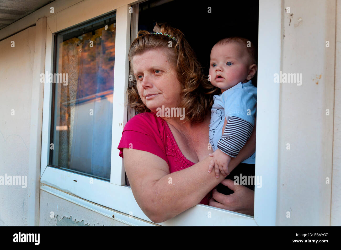 Internally displaced ethnic Croat woman and her grandson in prefabricated home at Tasovčići near Mostar, Bosnia - Stock Image