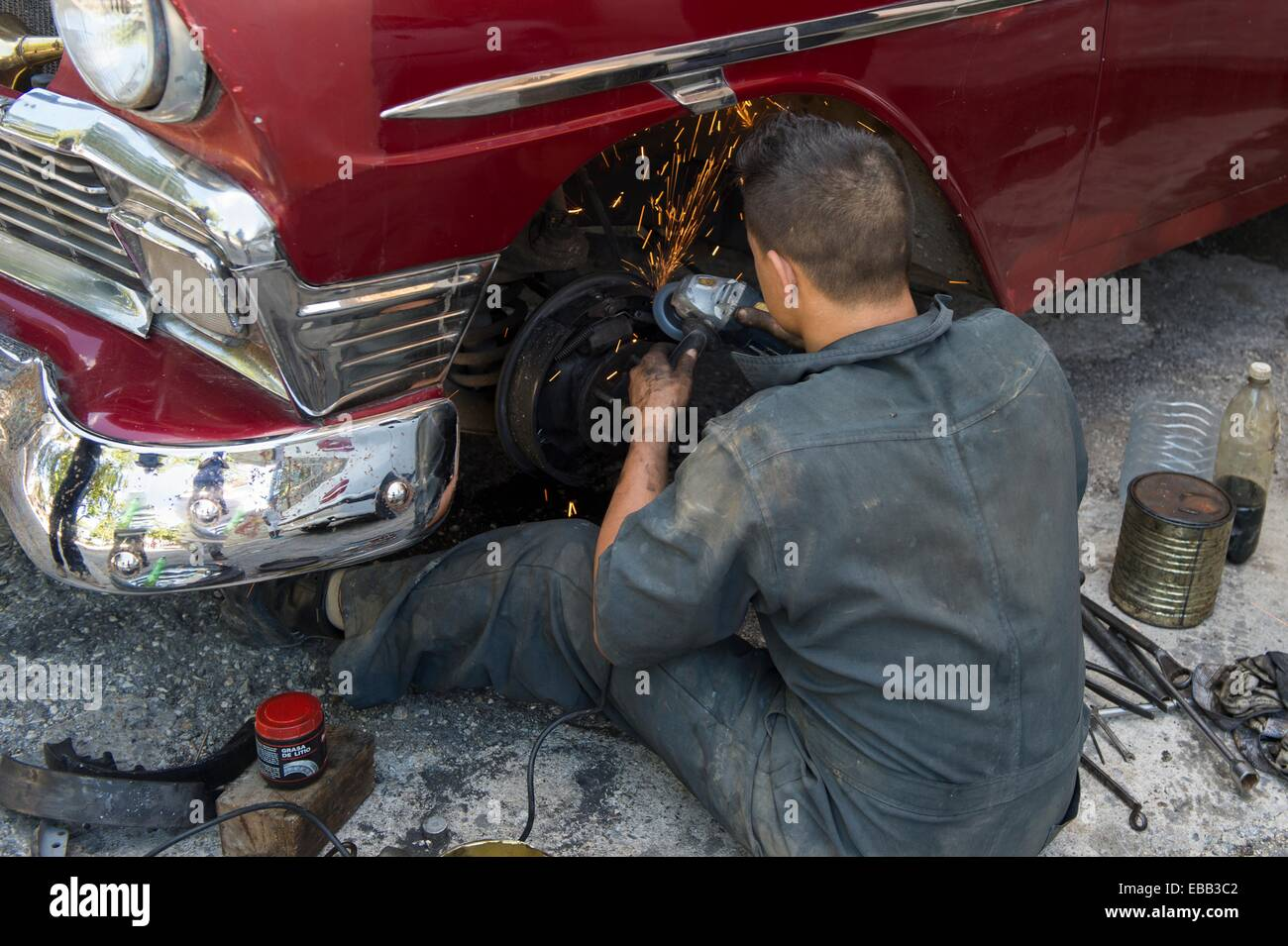 Car mechanic attempts to repair a Cuban classic on the street. Havana, Cuba. Stock Photo