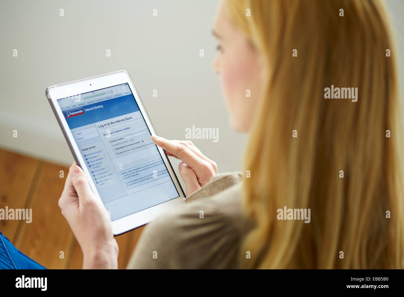 Woman banking online using an iPad - Stock Image