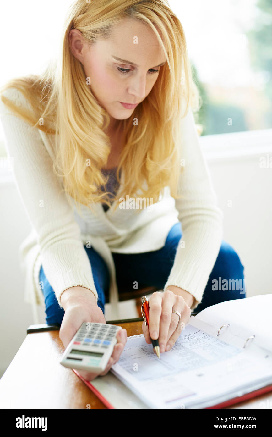 Woman working out finances - Stock Image