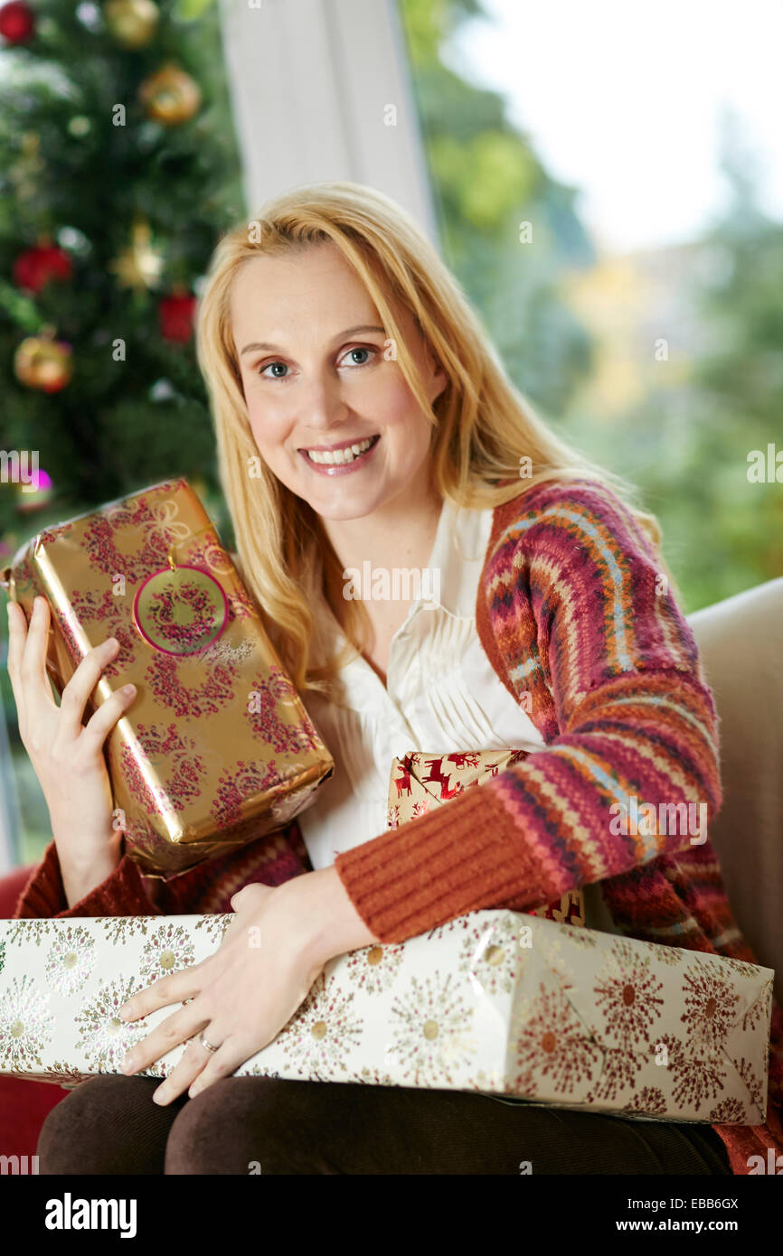 Happy woman sat with Christmas presents - Stock Image