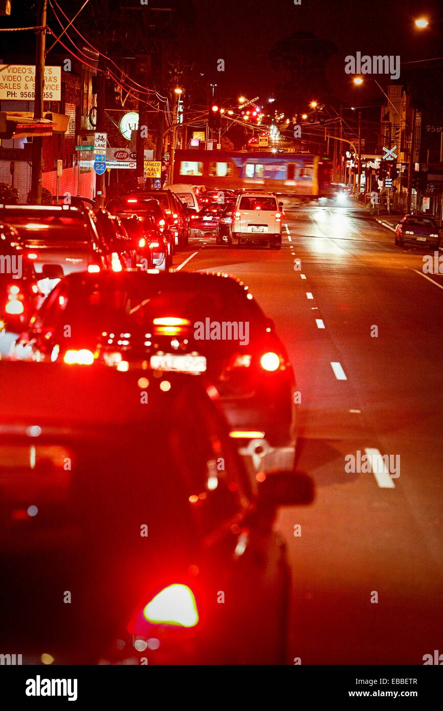Traffic congestion at railway crossing, red tail lights of cars, Melbourne Australia - Stock Image