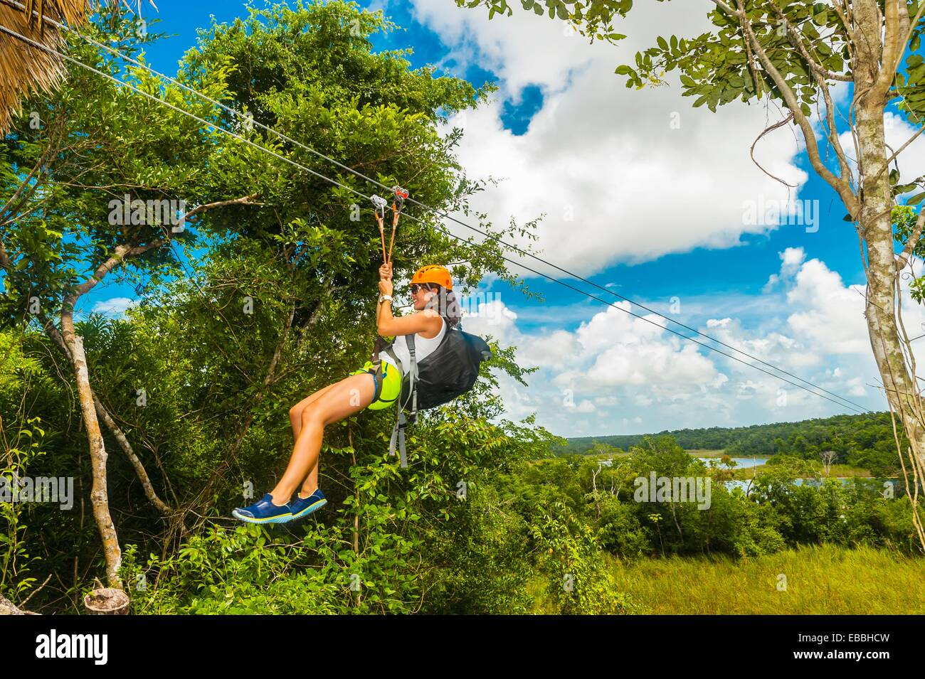A woman ziplining in the jungle with Alltournative Mayan Offtrack Adventures near Riviera Maya Mexico - Stock Image