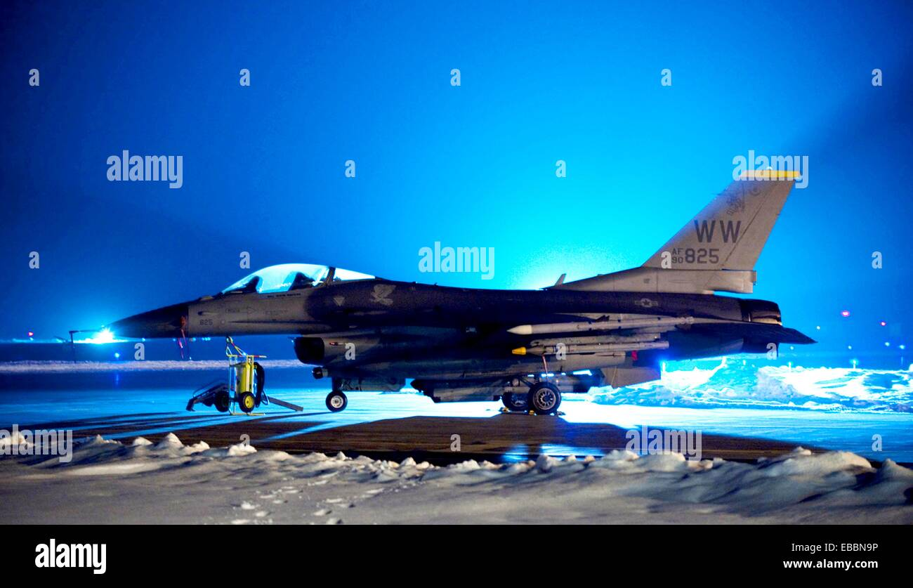 Floodlights illuminate an F-16 Fighting Falcon outside a hardened aircraft shelter at Misawa Air Base, Japan, Jan - Stock Image
