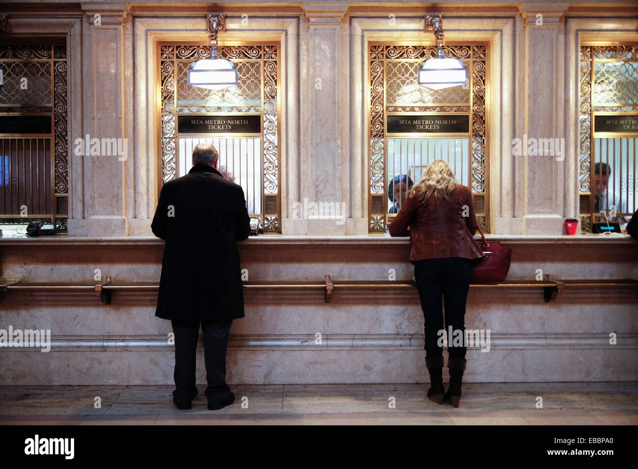 Man and Woman Separately Purchasing MTA-Metro North Commuter Railroad Tickets at Grand Central Station, New York, - Stock Image