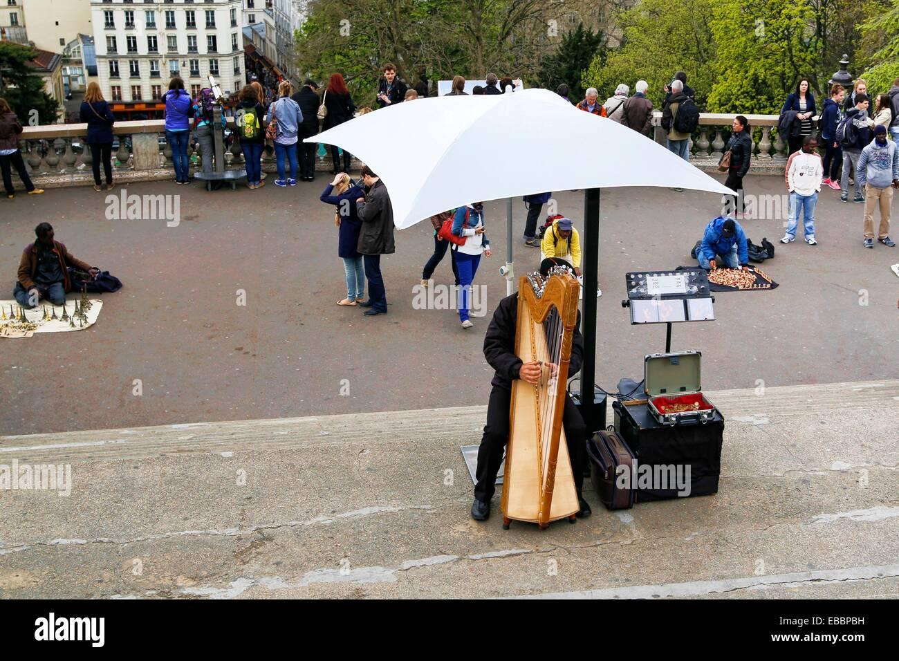 Street Performers including a Harpist Place du Parvis du Sacre Coeur Montmartre Area of Paris France. Stock Photo