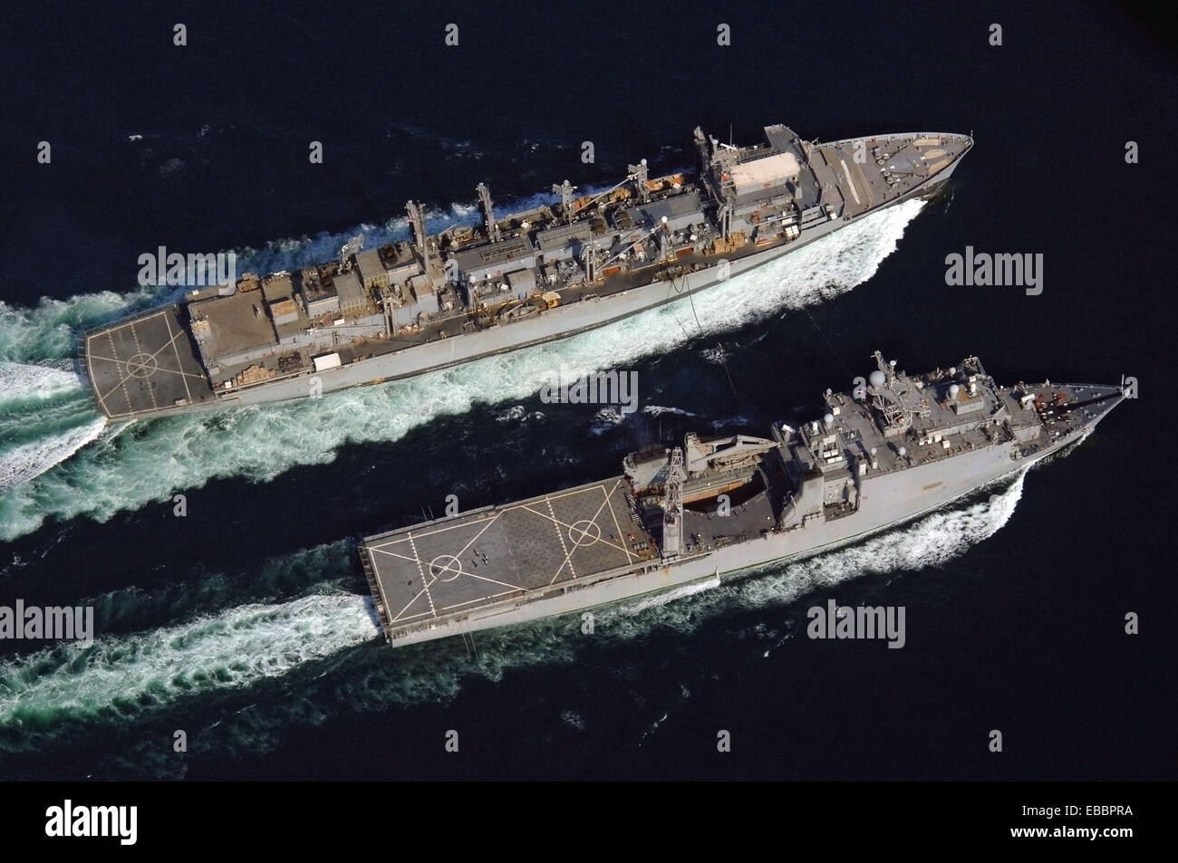 The fast combat logistic support ship USNS Supply (T-AOE 6), left, conducts an underway replenishment with USS Comstock - Stock Image