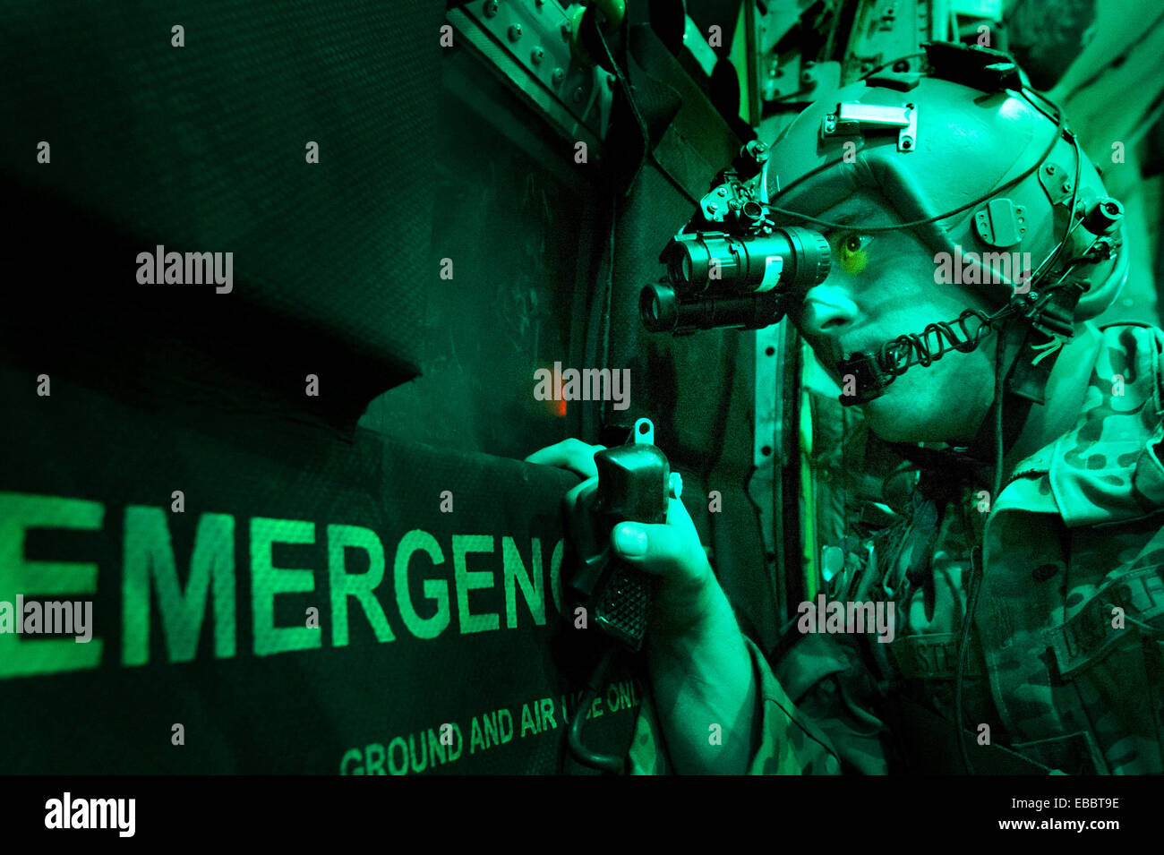 Senior Airman Larry Webster scans for potential threats using night vision goggles after completing a cargo airdrop - Stock Image