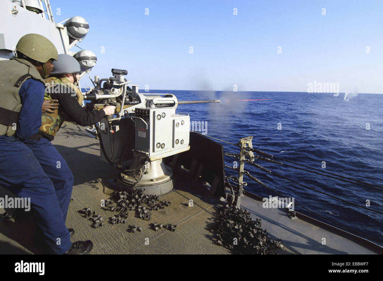 A Sailor fires a MK-38 25mm machine gun at the ´killer tomato´, a floating training target, during a live - Stock Image