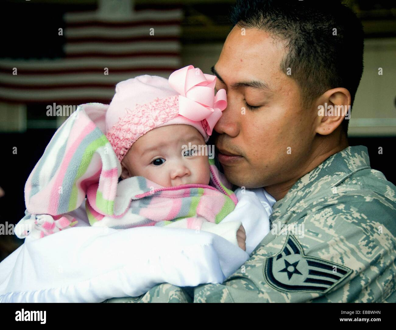 Staff Sgt. Dennis Horlador embraces his newborn, Natyala, after returning March 1 to Misawa Air Base, Japan. Sergeant - Stock Image