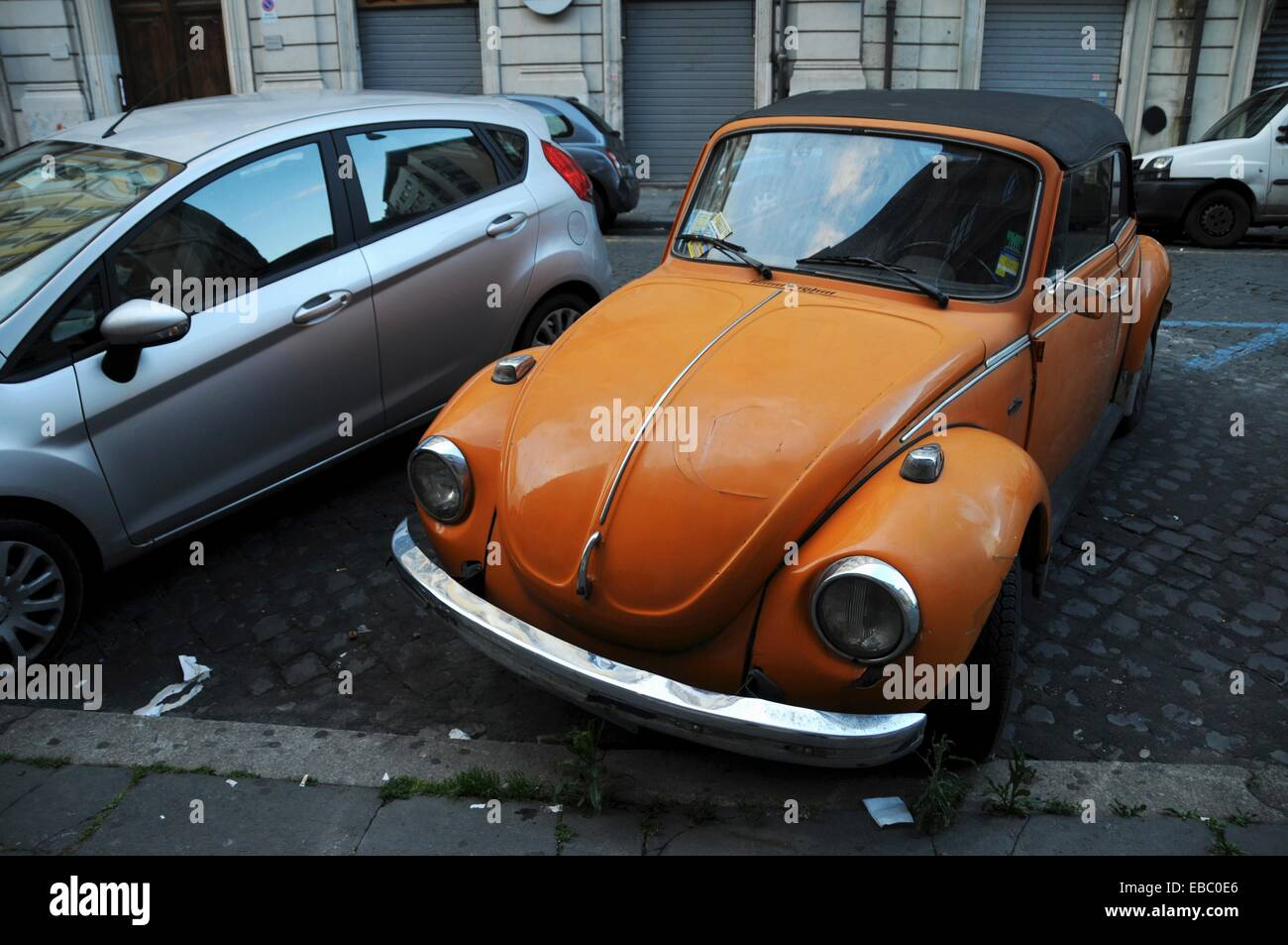 Old Orange VW Beetle in Rome - Stock Image