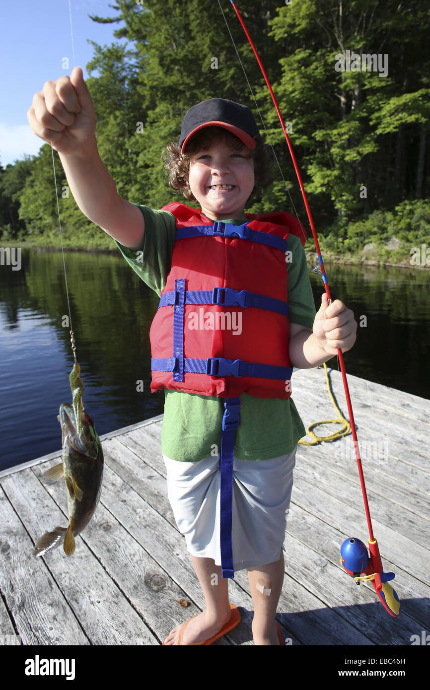 A 7 year old boy standing on a wharf holding a fishing rod and a fish that he caught - Stock Image