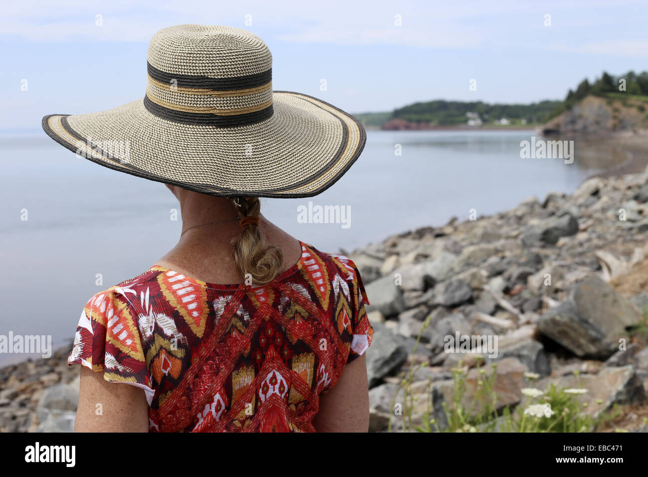A middle aged to senior woman with a wide brimmed hat viewing the Minas basin from Noel Nova Scotia canada - Stock Image