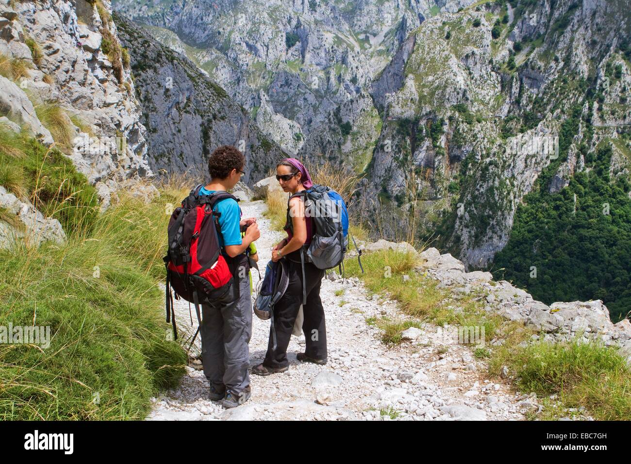 Hikers walking down from Tresviso, a small village in Picos de Europa National Park by historic Urdón path - Stock Image
