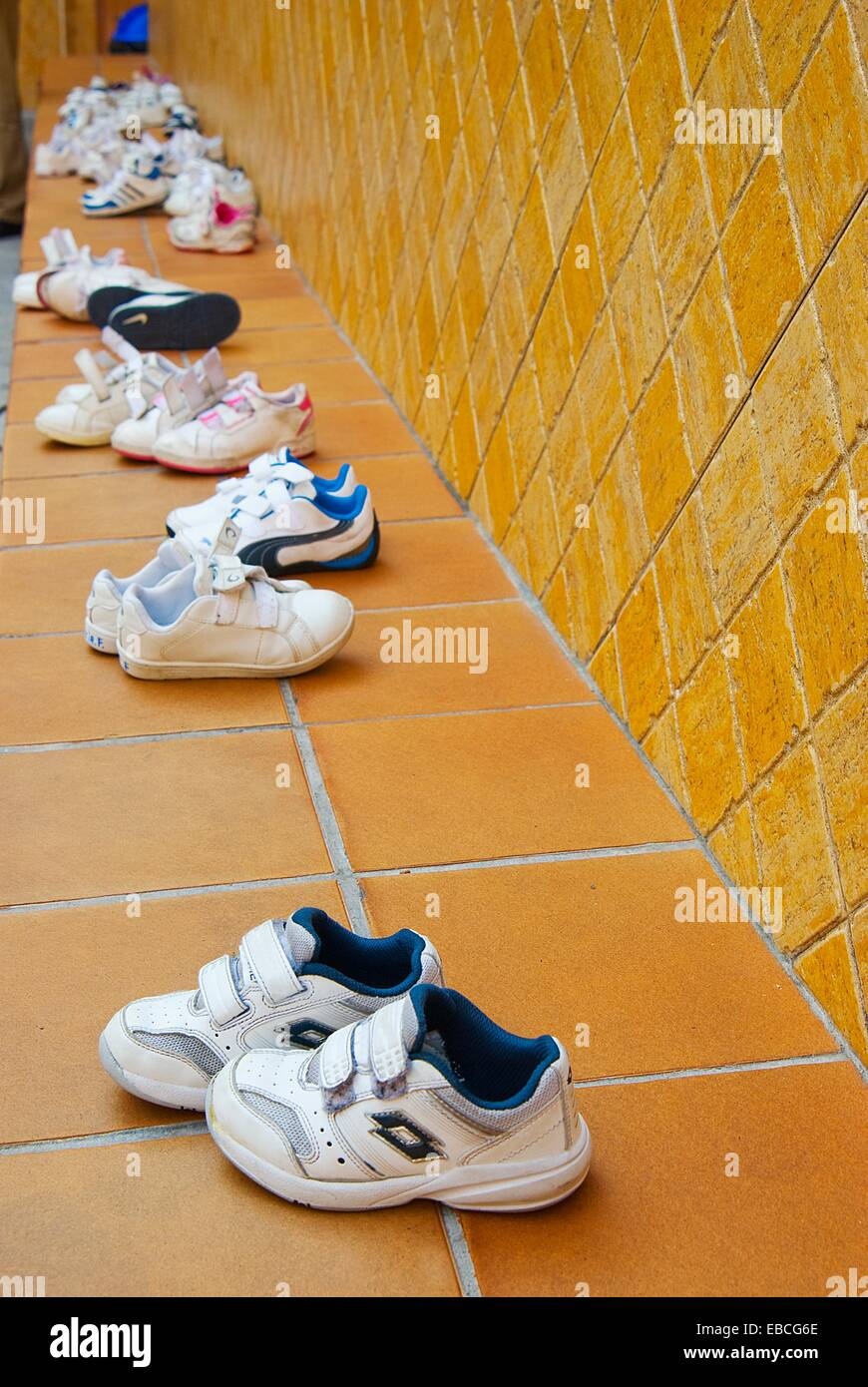 Children snickers shoes left on a bench - Stock Image