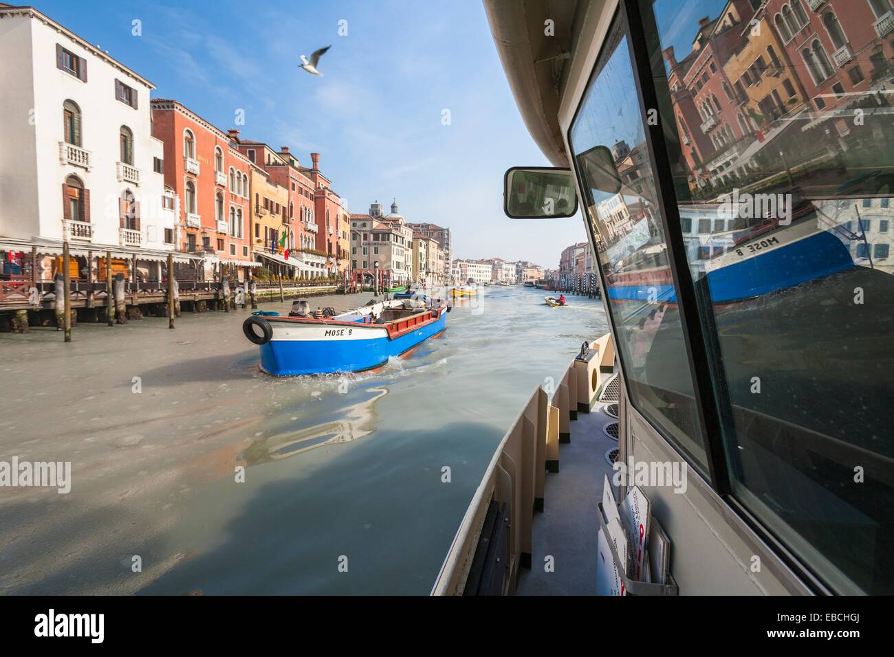 Trading boat and a Vaporetto on the Grand Canal (Canale Grande) Venice Italy Europe - Stock Image