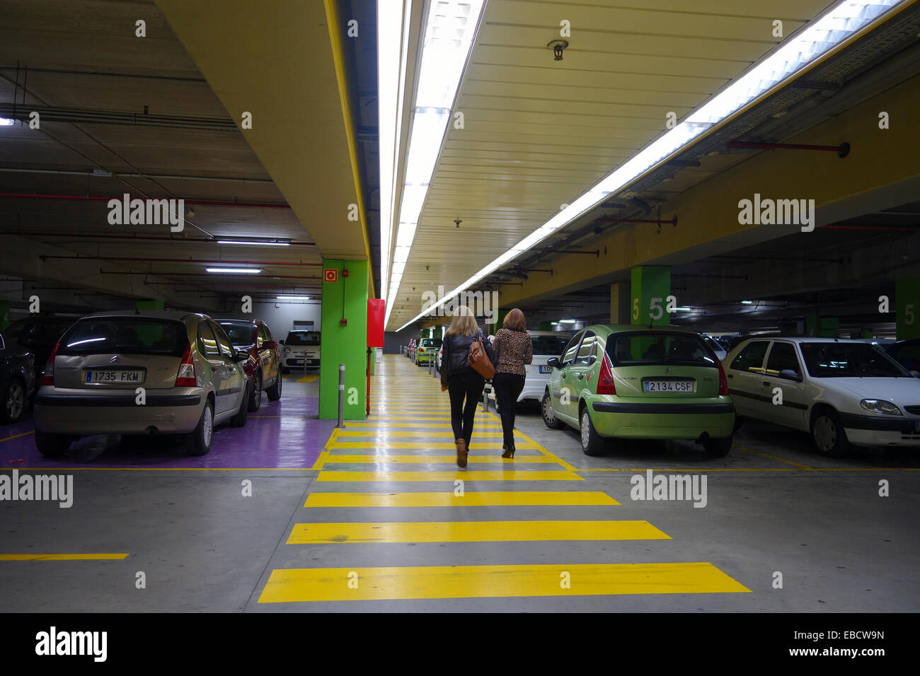 Two women walk in Underground Parking House with Parked cars, yellow dark. Spain - Stock Image