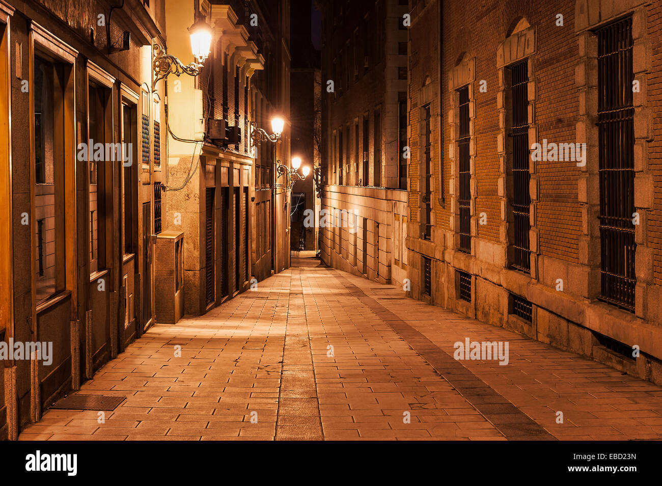 Narrow alley illuminated by street lamps at night, Madrid, Spain - Stock Image