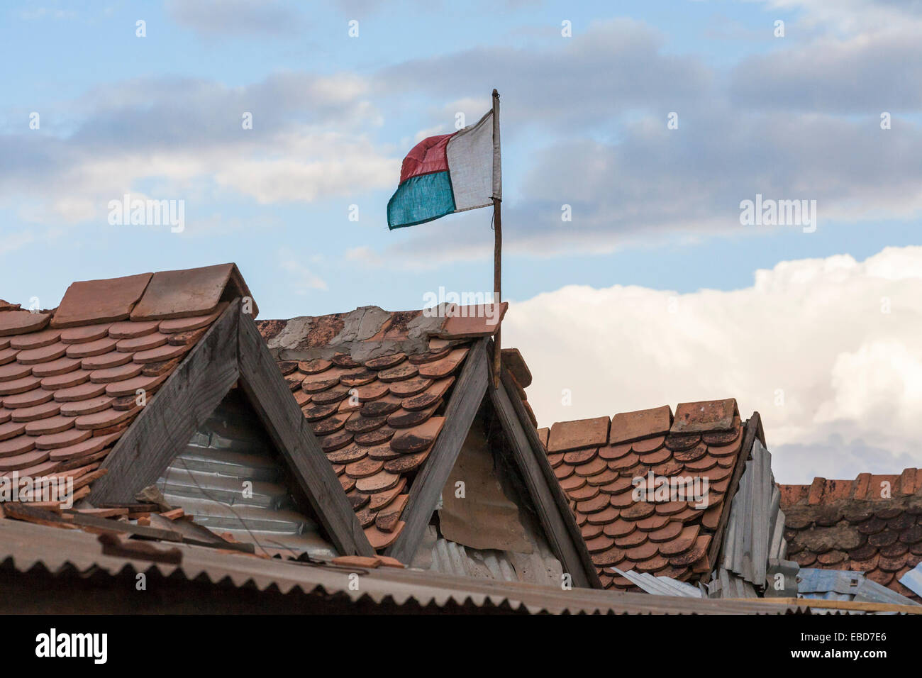 Madagascan national flag flying above the tiled roofs of buildings in Antananarivo, or Tana, capital city of Madagascar - Stock Image