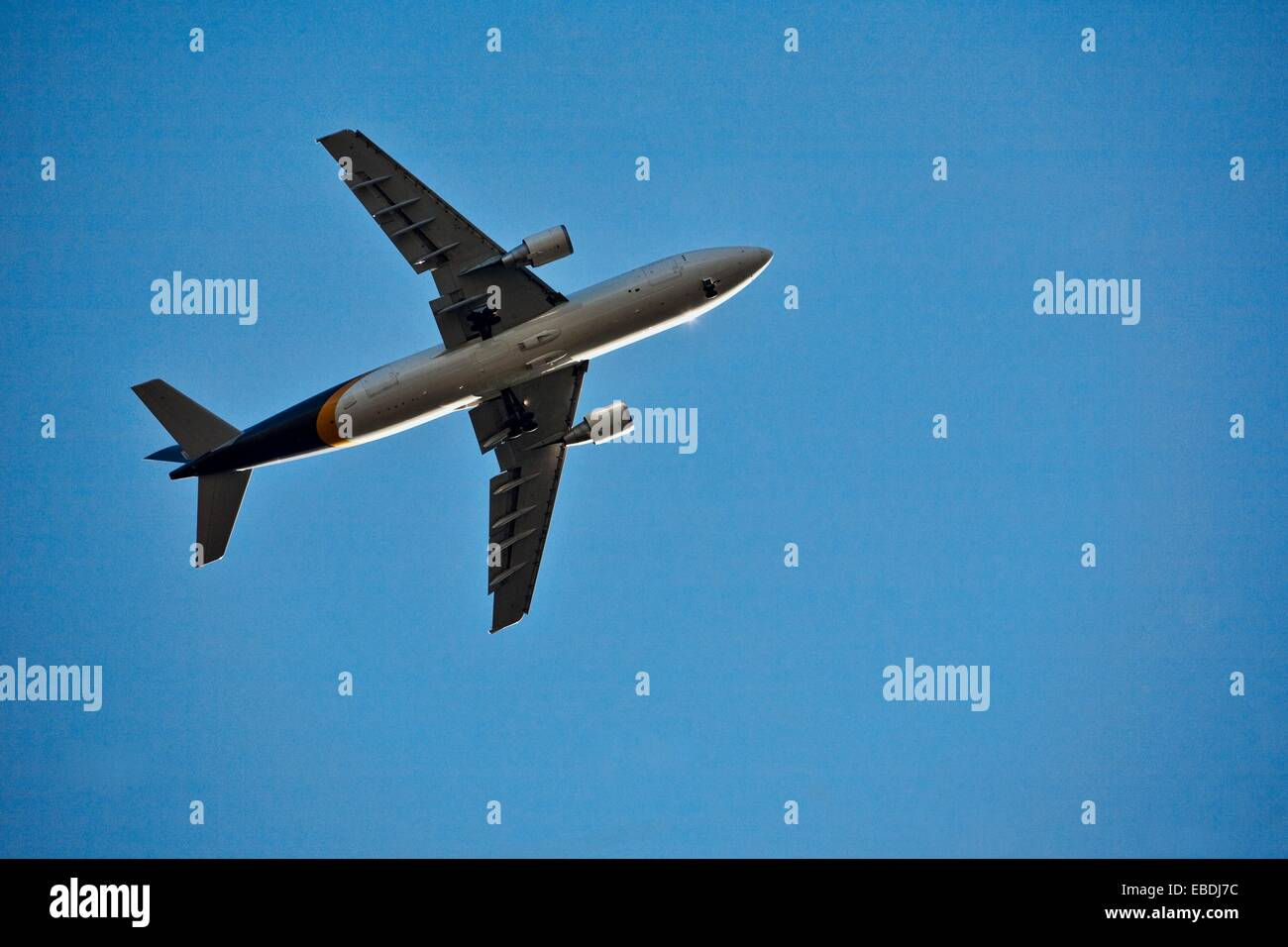 Image of commercial airliner shot from below with a blue sky in the background - Stock Image