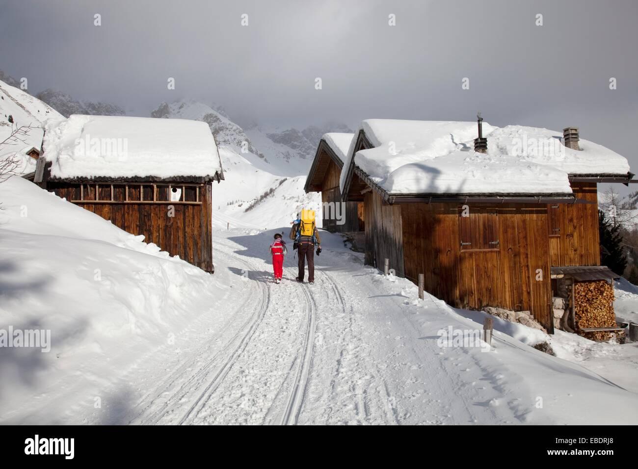 Snow trail alongside wooden barns, near Fuciade hut, San Pellegrino pass, Trentino Alto Adige, Italy, Europe Stock Photo