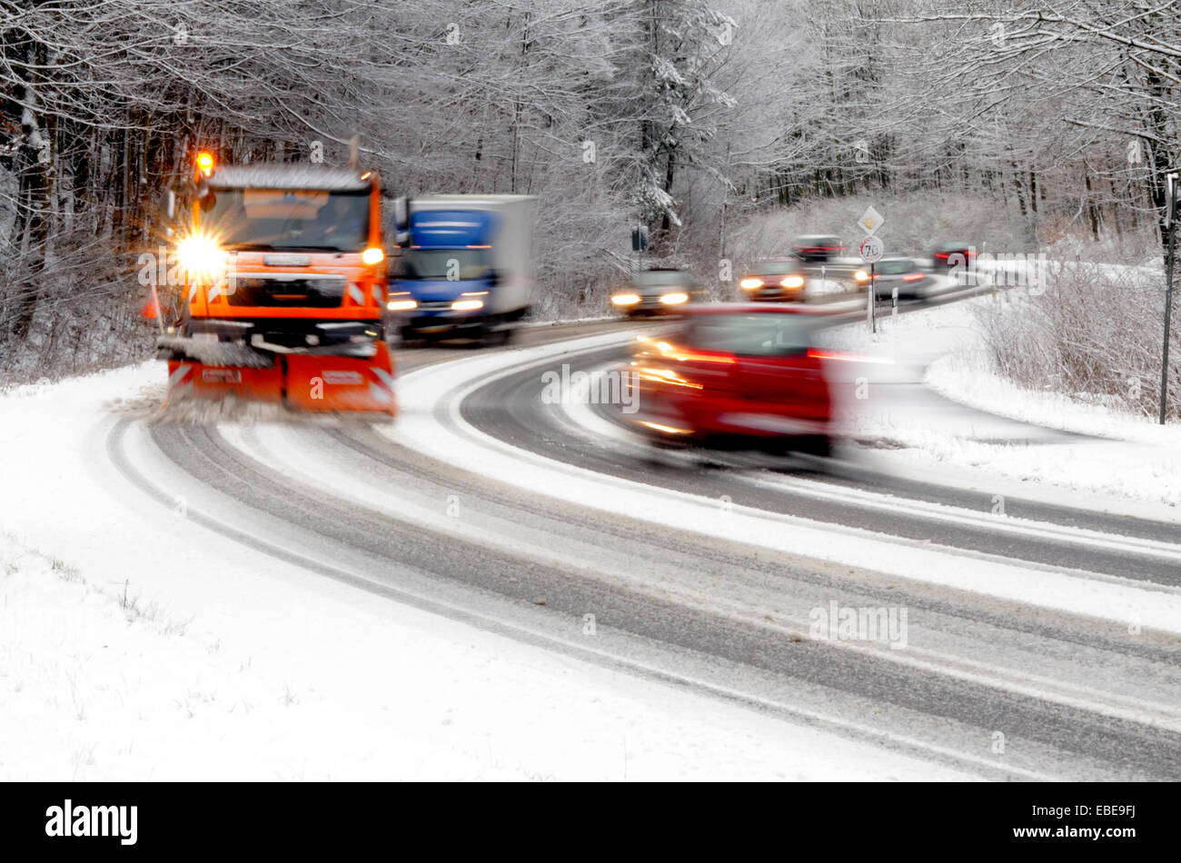 snowplow and cars on snowy winter road - Stock Image