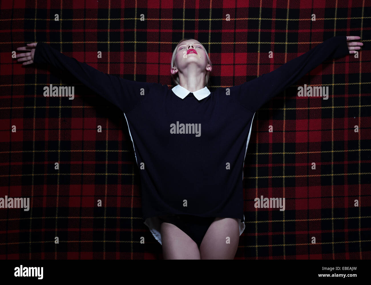 Woman in Dramatic Pose with Outstretched Hands over Purple Tartan - Stock Image