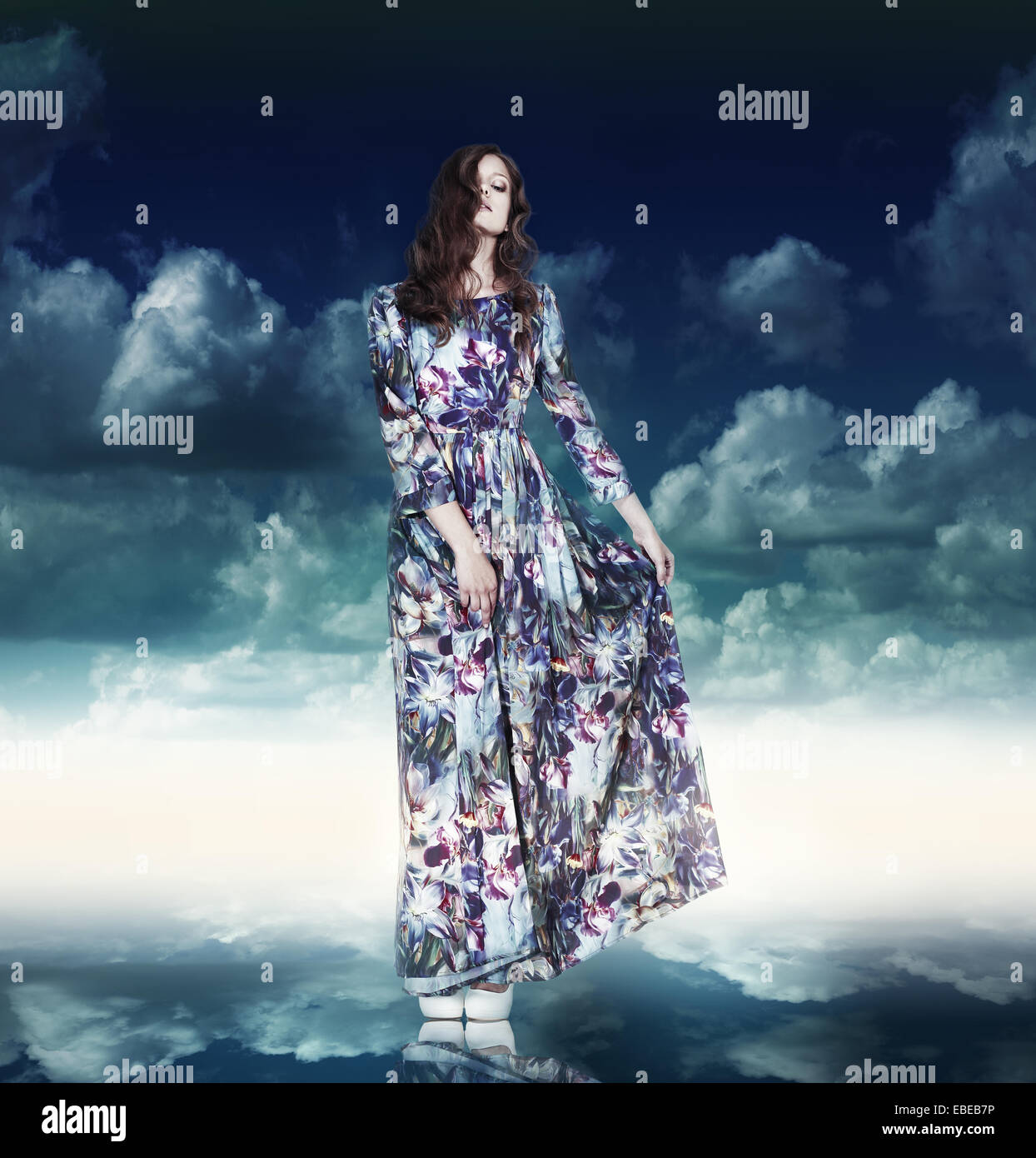 Fantasy. Luxurious Woman in Variegated Dress over Blue Sky - Stock Image
