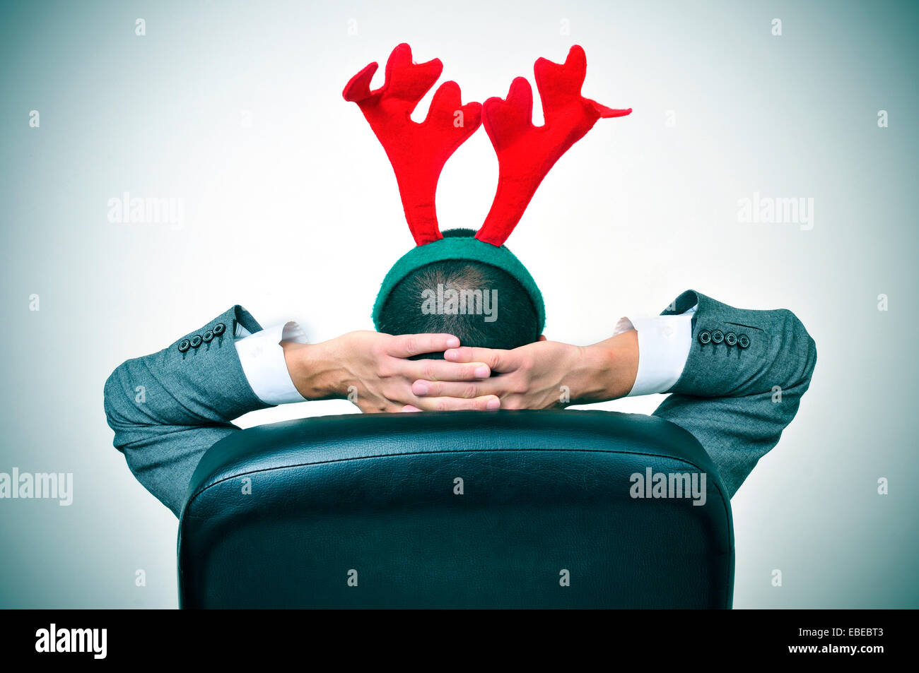 a man with a reindeer antlers headband relaxing in his office chair after an office christmas party - Stock Image