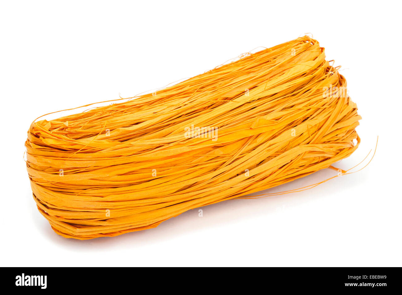 a skein of natural raffia dyed yellow on a white background - Stock Image