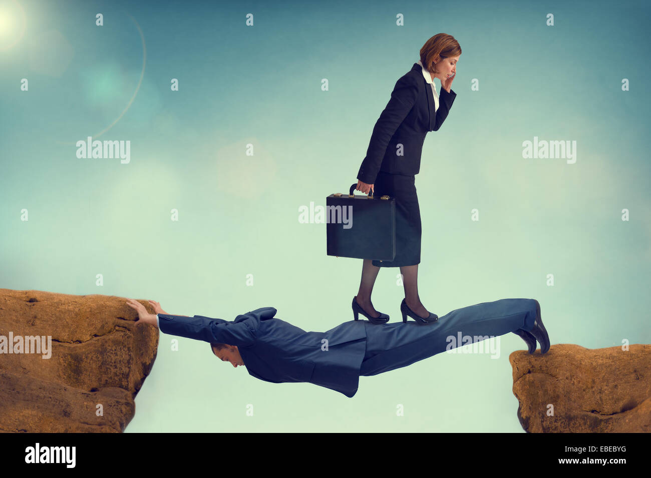 ruthless business woman walking over a vulnerable businessman - ambition concept - Stock Image