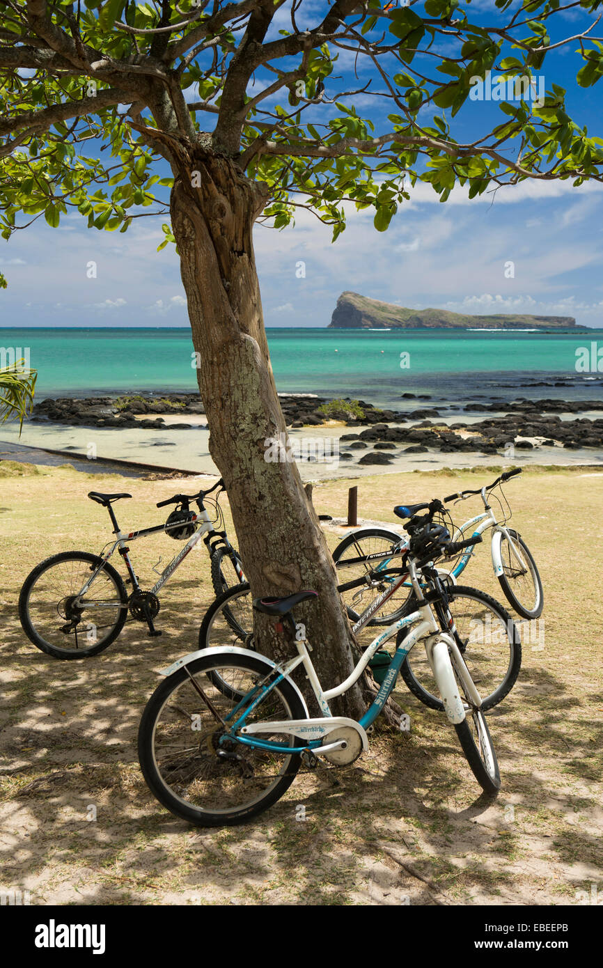 Mauritius, Cap Malheureux, bicycles in shade of tree opposite Coin de Mire island - Stock Image