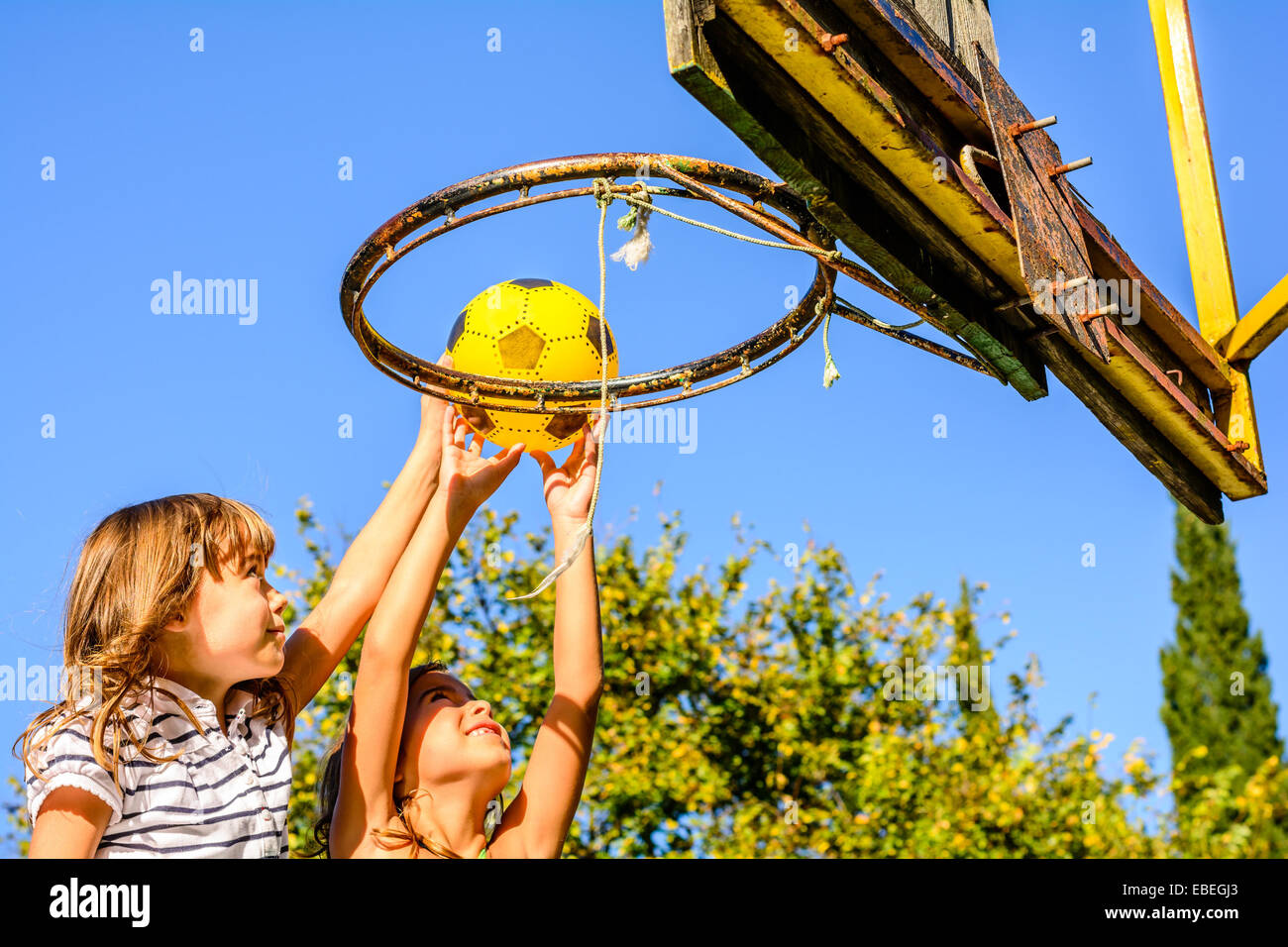 Two  seven year old girls playing basketball outdoors - Stock Image