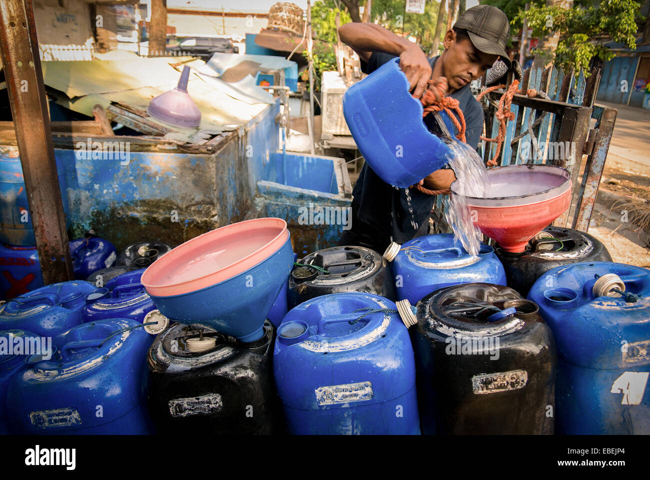 A man fills jerrycans on cart with water at a water distributor in Tanjung Priok, Jakarta, Indonesia. - Stock Image