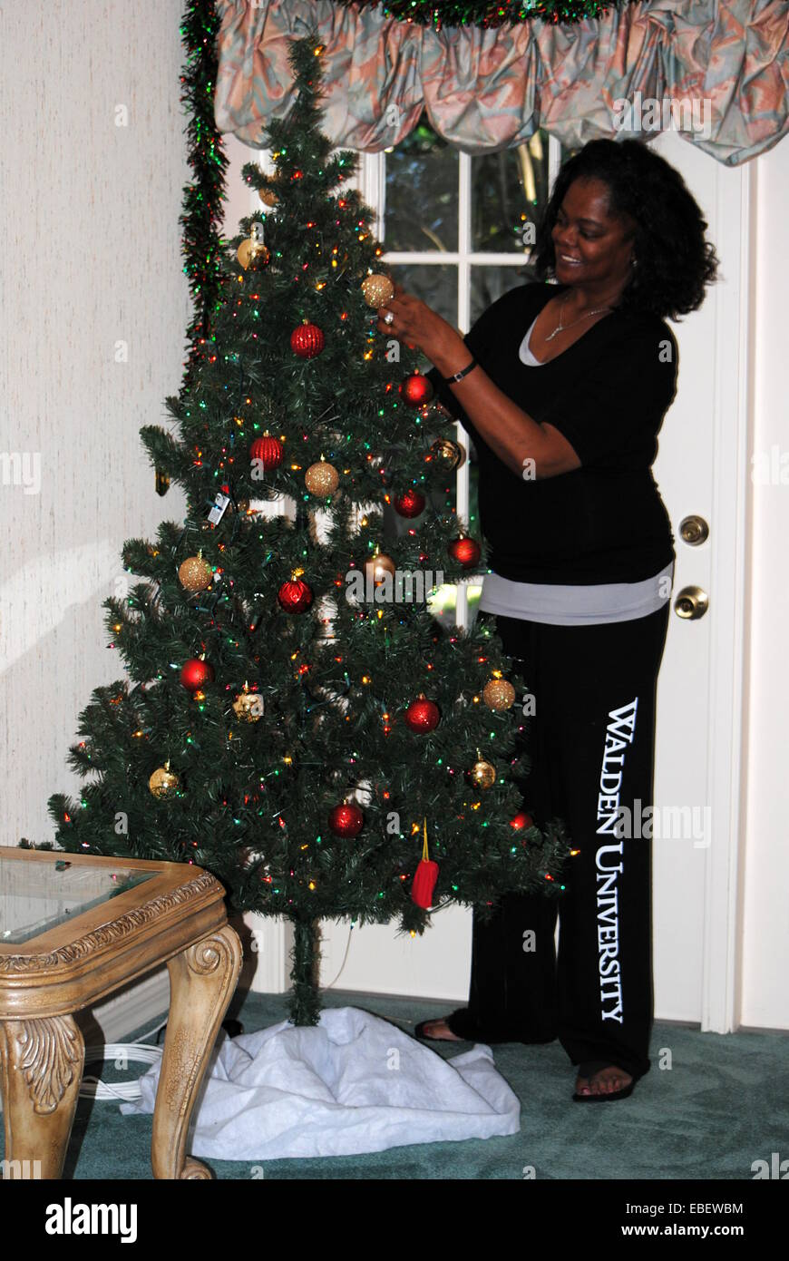 Decorating Christmas Tree at home,getting it ready for gifts and presents.  A scene of complete domestic bliss. - Stock Image