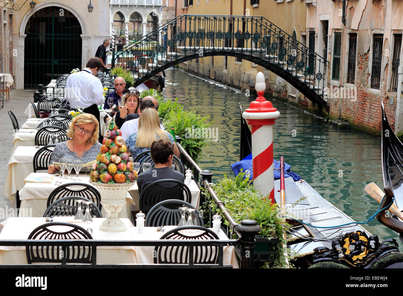 Venice Sestiere San Marco a waiter serves tourists along a small canal - Stock Image