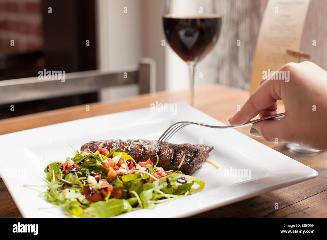 Female hand with fork and grilled steak with red wine - Stock Image