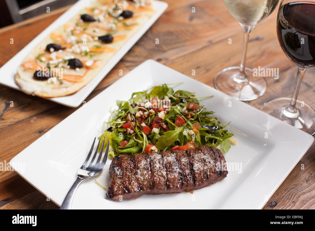 Grilled steak with arugula salad and rustic flatbread with wine - Stock Image