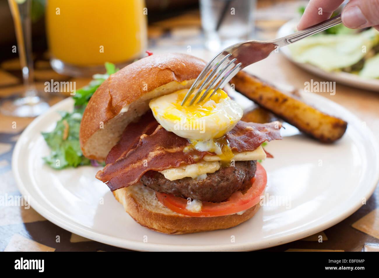 Fork breaking yoke on a breakfast burger - Stock Image