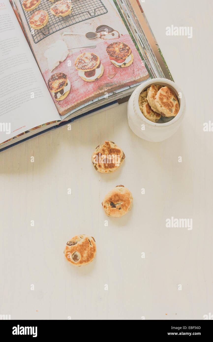 Just baked home made Welsh cakes next to recipe book. - Stock Image