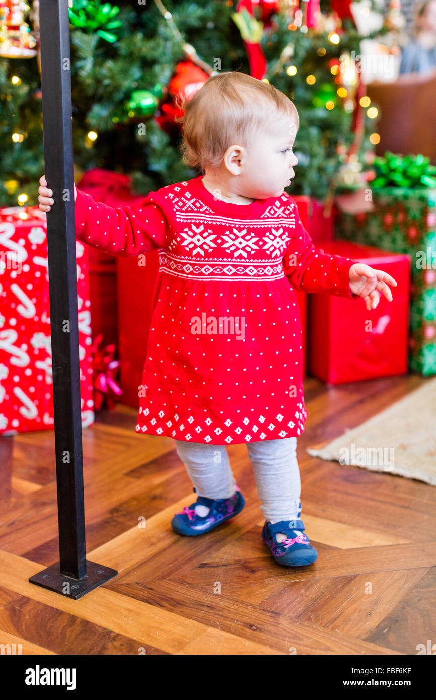 7945be5b8 Cute baby girl in Scandinavian red dress next to Christmas tree ...