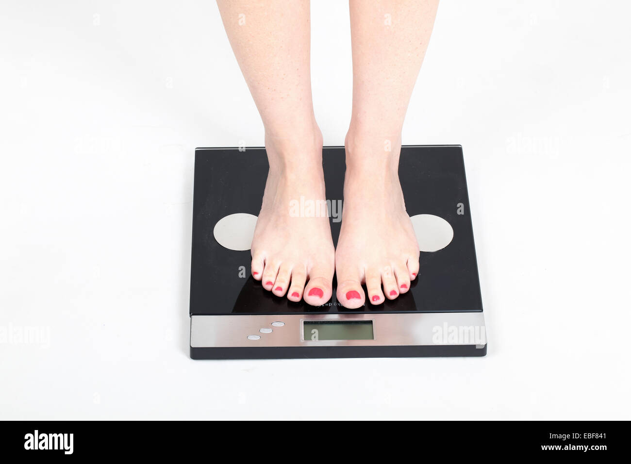 Woman's feet on scale Model released - Stock Image